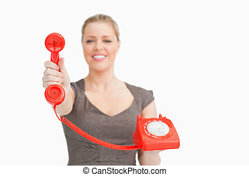 Woman showing a red retro phone