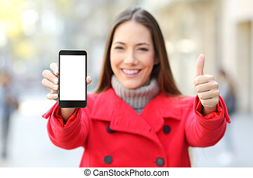 Woman showing a smart phone screen in winter on a street