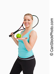 Woman showing a tennis ball in her hand