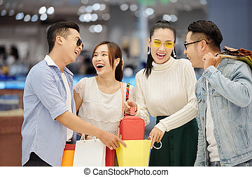 woman showing bag to cheerful friends