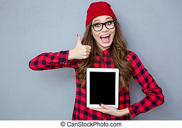 Woman showing blank tablet computer screen and thumb up