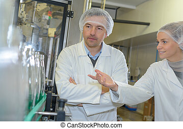 Woman showing bottling plant to man