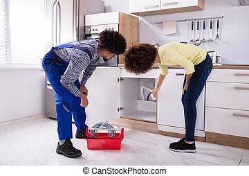 Woman Showing Damaged Sink Pipe To Plumber