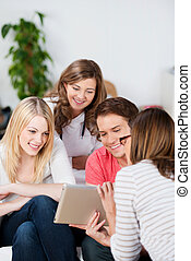 Woman Showing Digital Tablet To Friends At Home