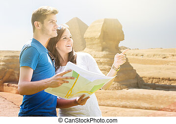 Woman Showing Direction To Man Holding Map