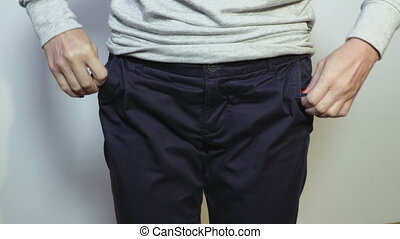 Woman showing empty pockets of trousers demonstrating she ...