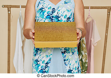 Woman showing golden box