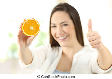 Woman showing half orange with thumbs up