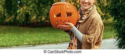 woman showing Halloween pumpkin Jack O?Lantern