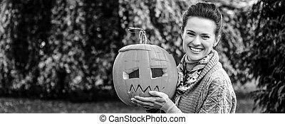 woman showing Halloween pumpkin Jack O'Lantern