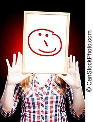 Woman showing happy emoticon in front of face
