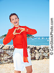 Woman showing heart shaped hands in front of lagoon with yachts