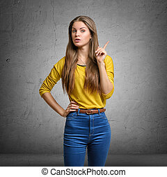 Woman showing her index finger with serious expression to make a warning sign