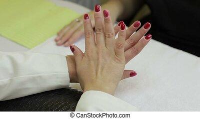 Woman showing her red gel manicure in beauty salon - Closeup...
