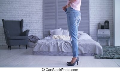 Woman showing her weightloss by wearing old jeans -...