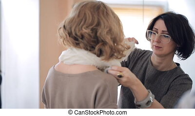 Woman showing how to tie a scarf around the neck of the model
