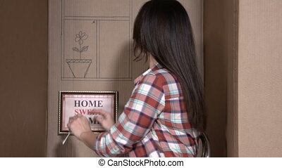Woman showing keys of her new apartment sitting in a cardboard box