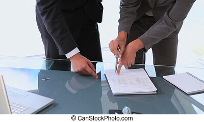 Woman showing man where to sign in a contract