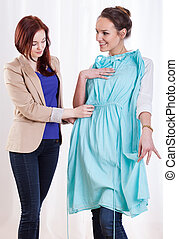 Woman showing new dress to her friend