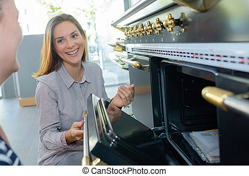 Woman showing oven to customer