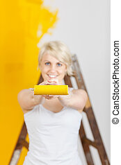 Woman Showing Paint Roller With Yellow Paint