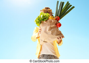 woman showing paper bag with groceries against blue sky