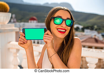 Woman showing phone with empty screen on beautiful white city background