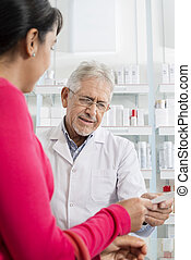 Woman Showing Prescription To Chemist In Pharmacy