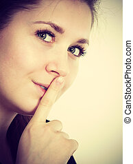Woman showing silence gesture with finger