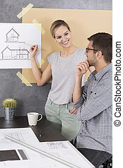Woman showing something on a drawing to her co-worker