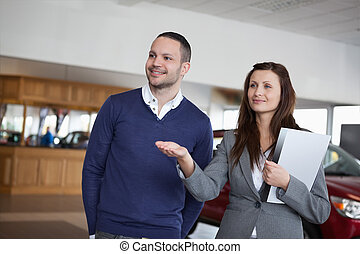 Woman showing something to a man in a dealership
