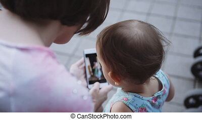 Woman showing something to her child on the smartphone.