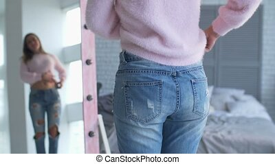 Woman showing successful weight loss with her jeans