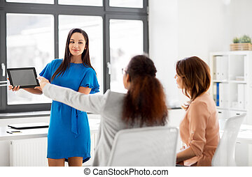 woman showing tablet pc to business team at office