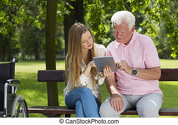 Woman showing the older man a tablet