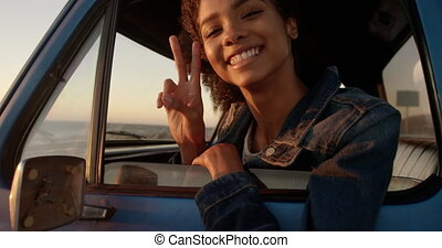 Woman showing victory sign in pickup truck at beach 4k - ...