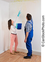 Woman Showing Water Leaking From Ceiling To Maintenance Guy
