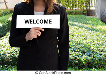 Woman showing white sign with welcome word