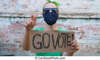 Woman shows cardboard with Go Vote sign on brick wall urban ...