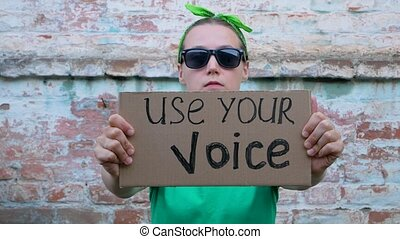Woman shows cardboard with Use Your Voice sign on brick wall...