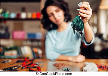 Woman shows handmade bracelet, needlework hobby