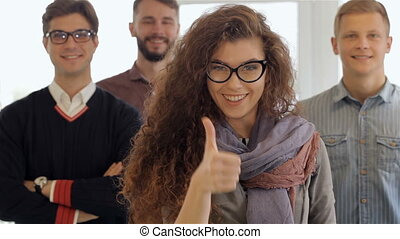 Woman shows her thumb up in front of three men at the office
