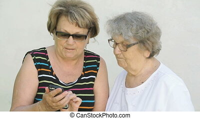 Woman shows photo to old woman using a smartphone