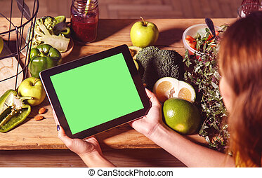 Woman Shows Tablet at Kitchen Table