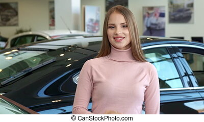 Woman shows the car key at the dealership - Pretty young...