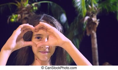 Woman shows the heart shape with the fingers on the...