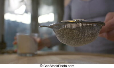 Woman sifting flour through a sieve in the kitchen