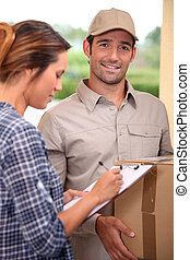 Woman signing for a courier delivered parcel