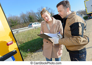 woman signing insurance paperwork after a car breakdown