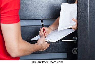 Woman signing package delivery papers - Woman signing parcel...